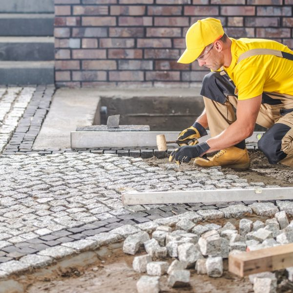 Professional Caucasian Worker Building Granite Paved Hardstandin